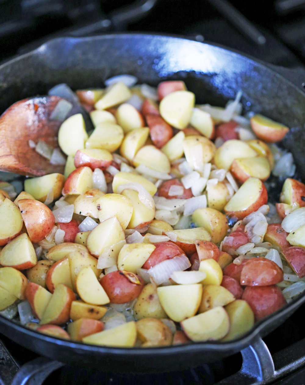 Sautéed onions and chopped baby potatoes in a cast iron skillet.