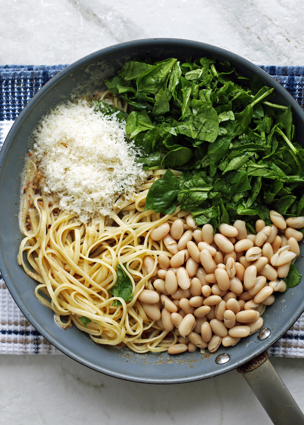 Pasta, white beans, spinach, and parmesan cheese placed on top of a brown butter sauce that's in a large skillet.