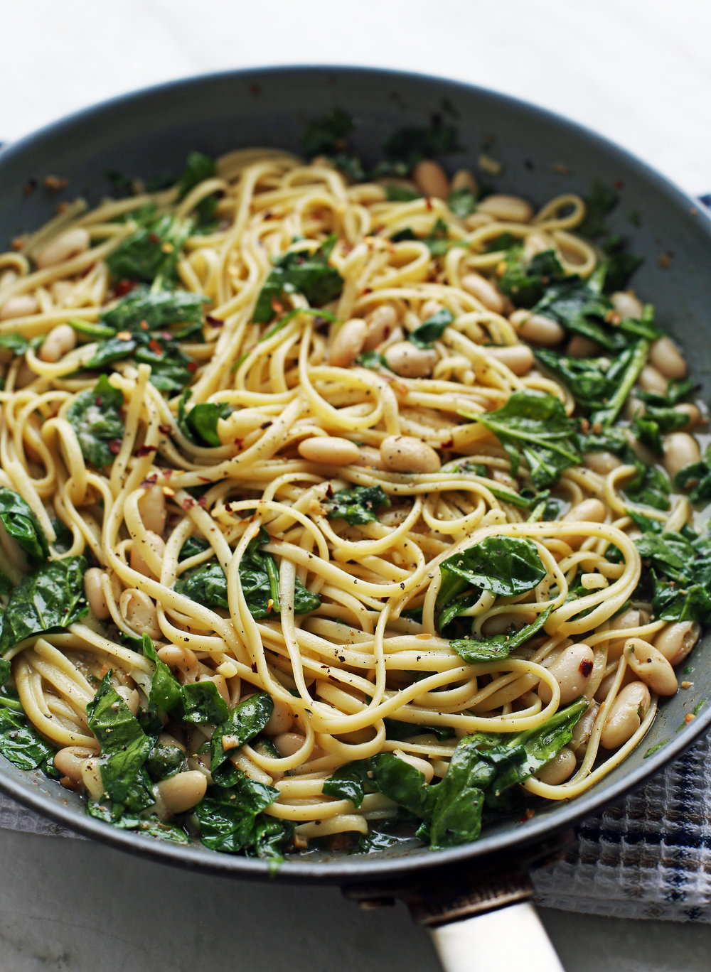 Tossed brown butter linguine pasta with spinach and white beans in a large skillet.