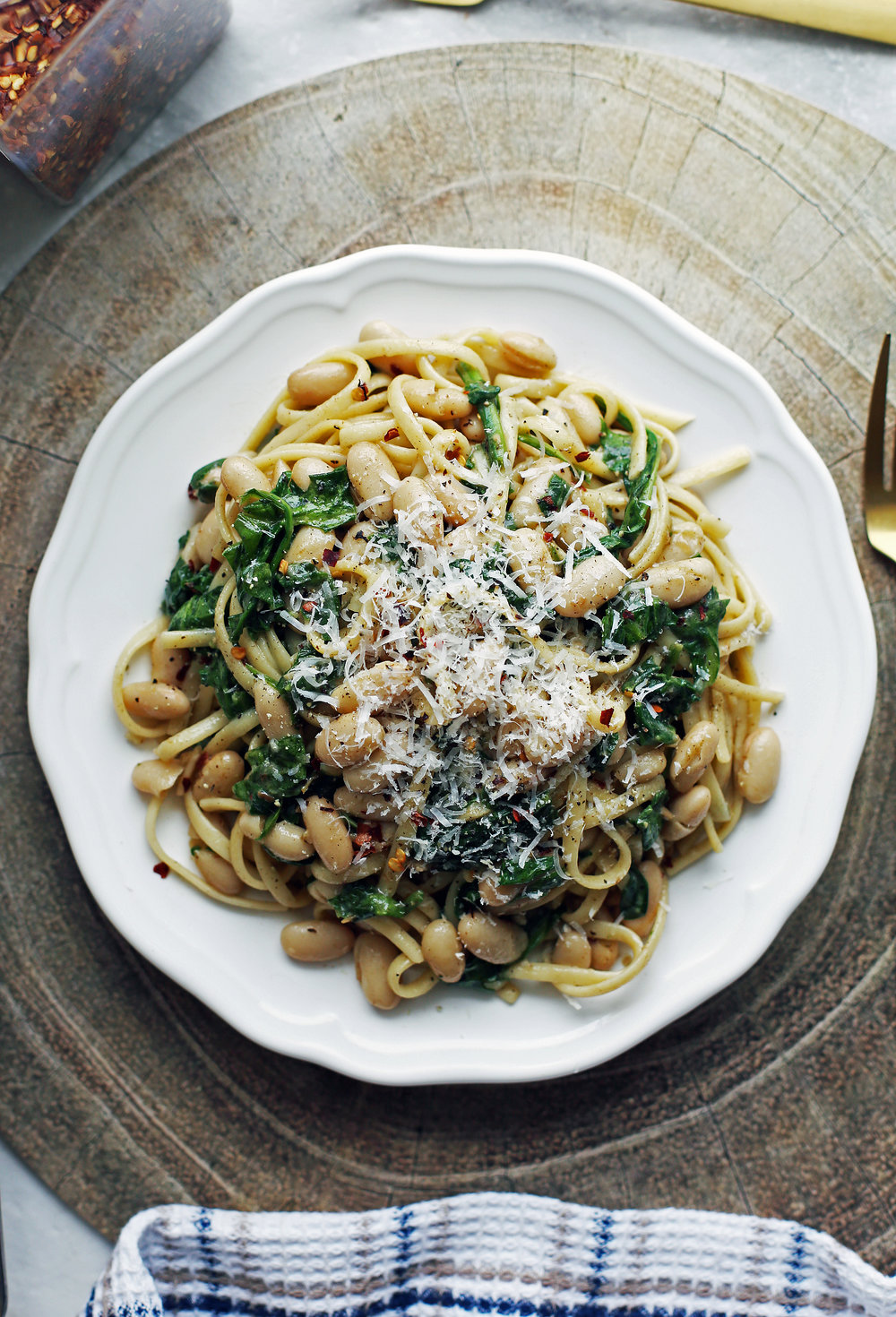 Overhead view of Brown Butter Linguine with White Beans and Spinach topped with parmesan cheese on a white plate.
