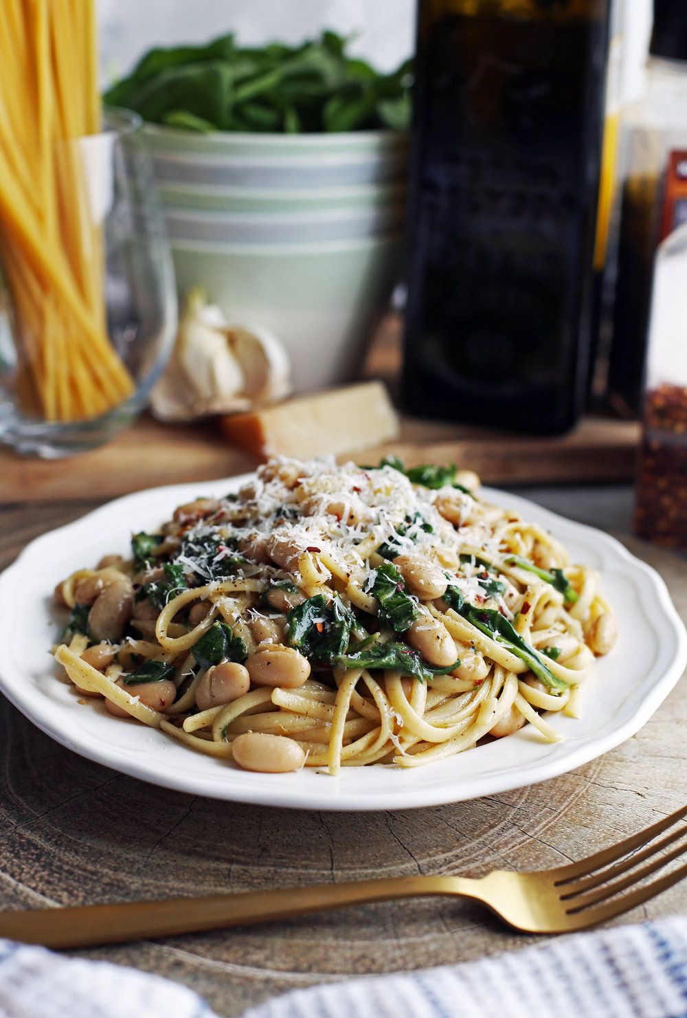 A white plate full of Brown Butter Linguine with White Beans and Spinach topped with parmesan cheese.