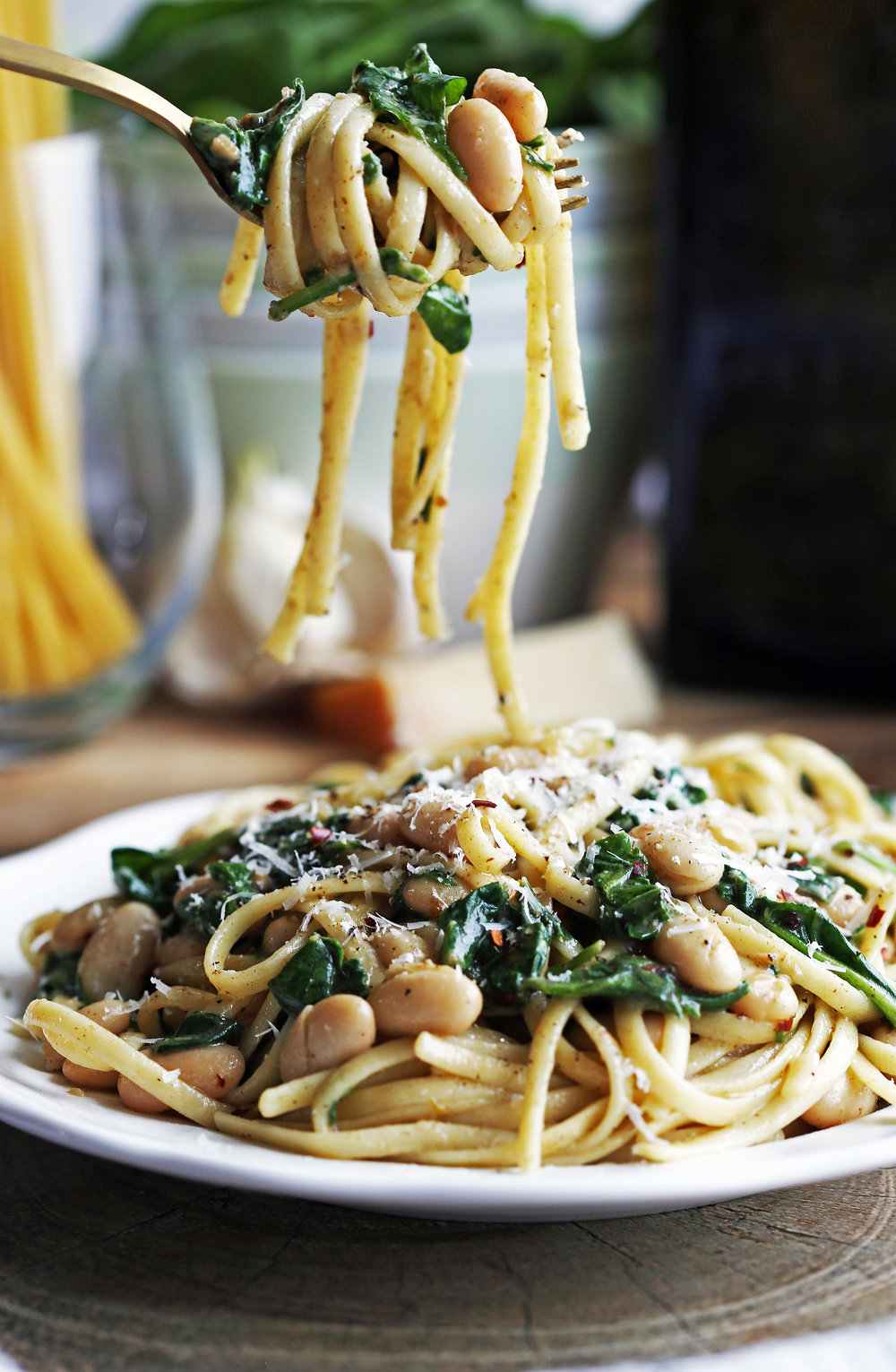 Brown Butter Linguine with White Beans and Spinach twirled on a gold fork with a plateful of the same pasta below.