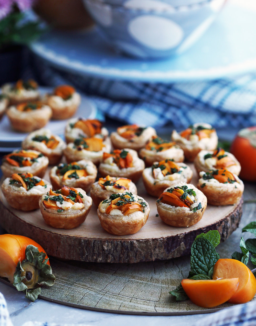 Over a dozen Persimmon Goat Cheese Tartlets garnished with fresh mint on a wooden platter.
