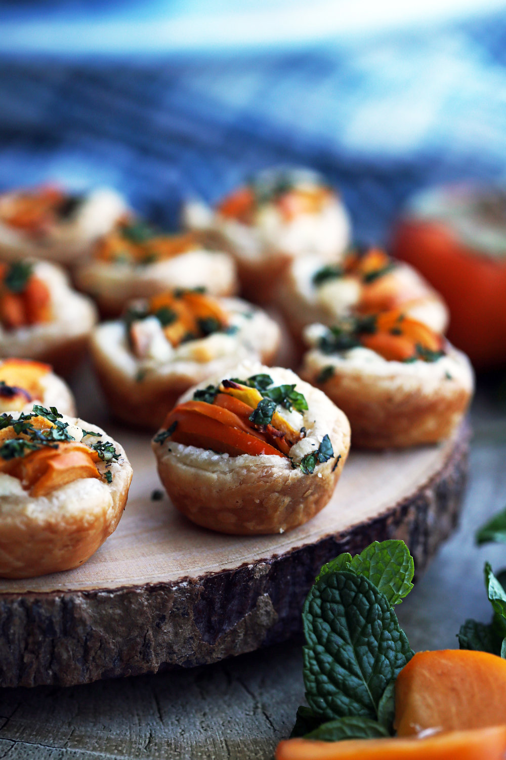 A closeup of a Persimmon Goat Cheese Tartlet surrounded by more tartlets on a wooden platter.
