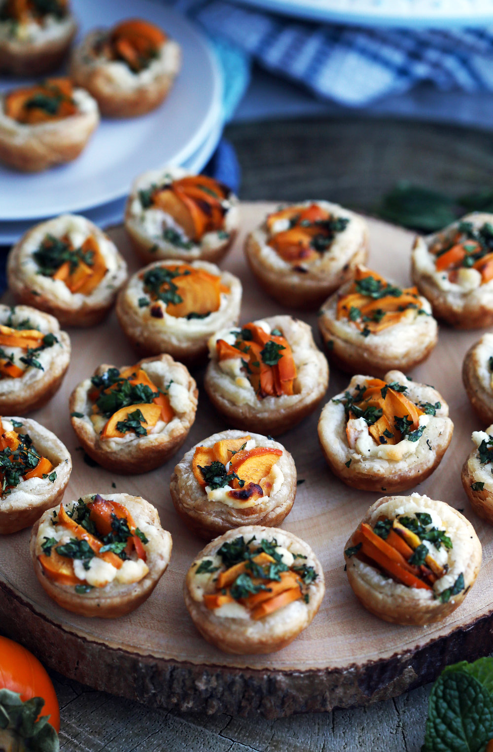 Persimmon Goat Cheese Tartlets with fresh mint topping on a large round wooden platter.