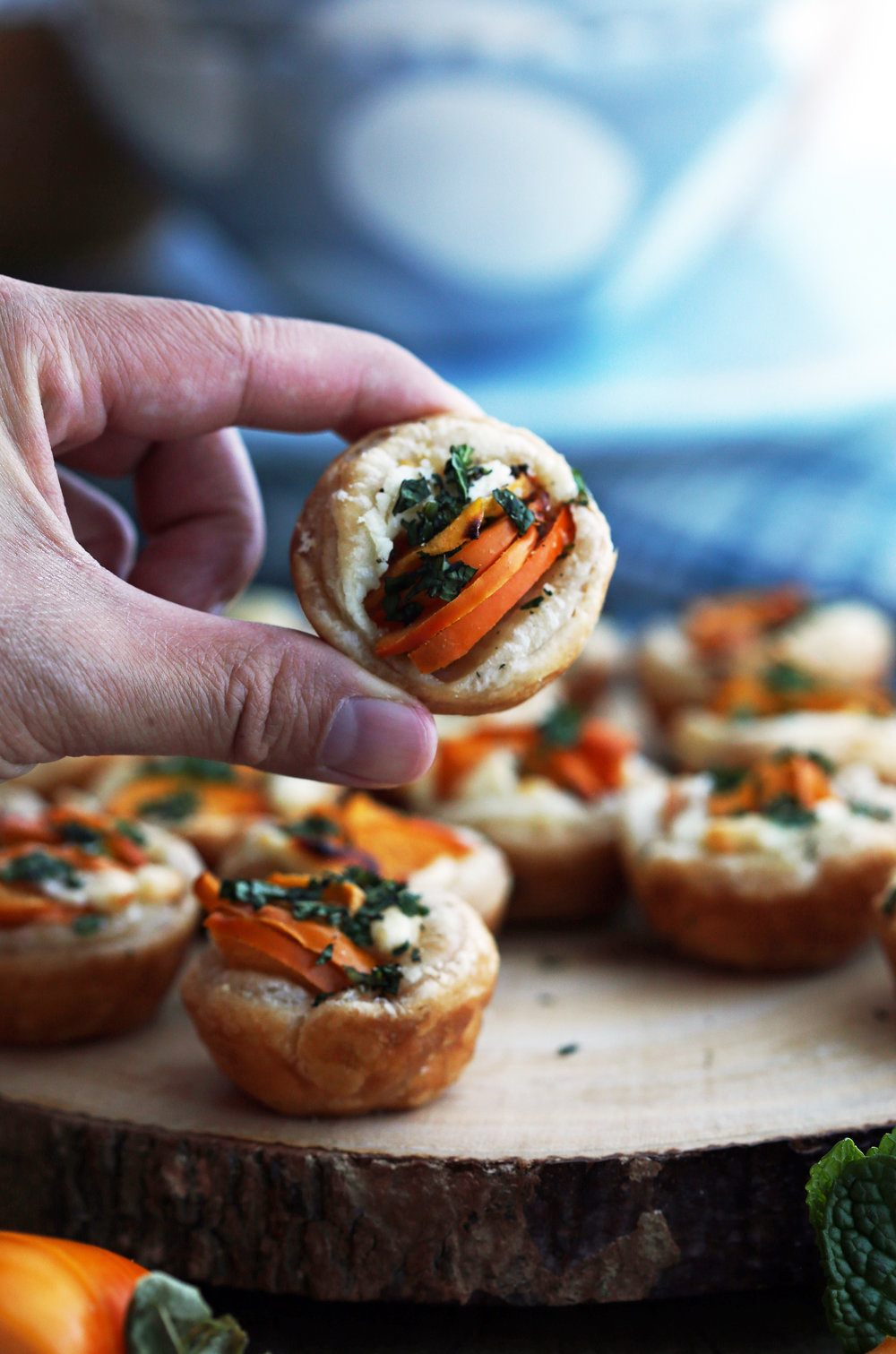 A hand holding a single Persimmon Goat Cheese Tartlet over a wooden platter full of more tartlets.