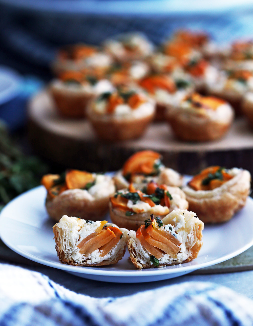 Five Persimmon Goat Cheese Tartlets on a white plate with one tartlet cut in half.