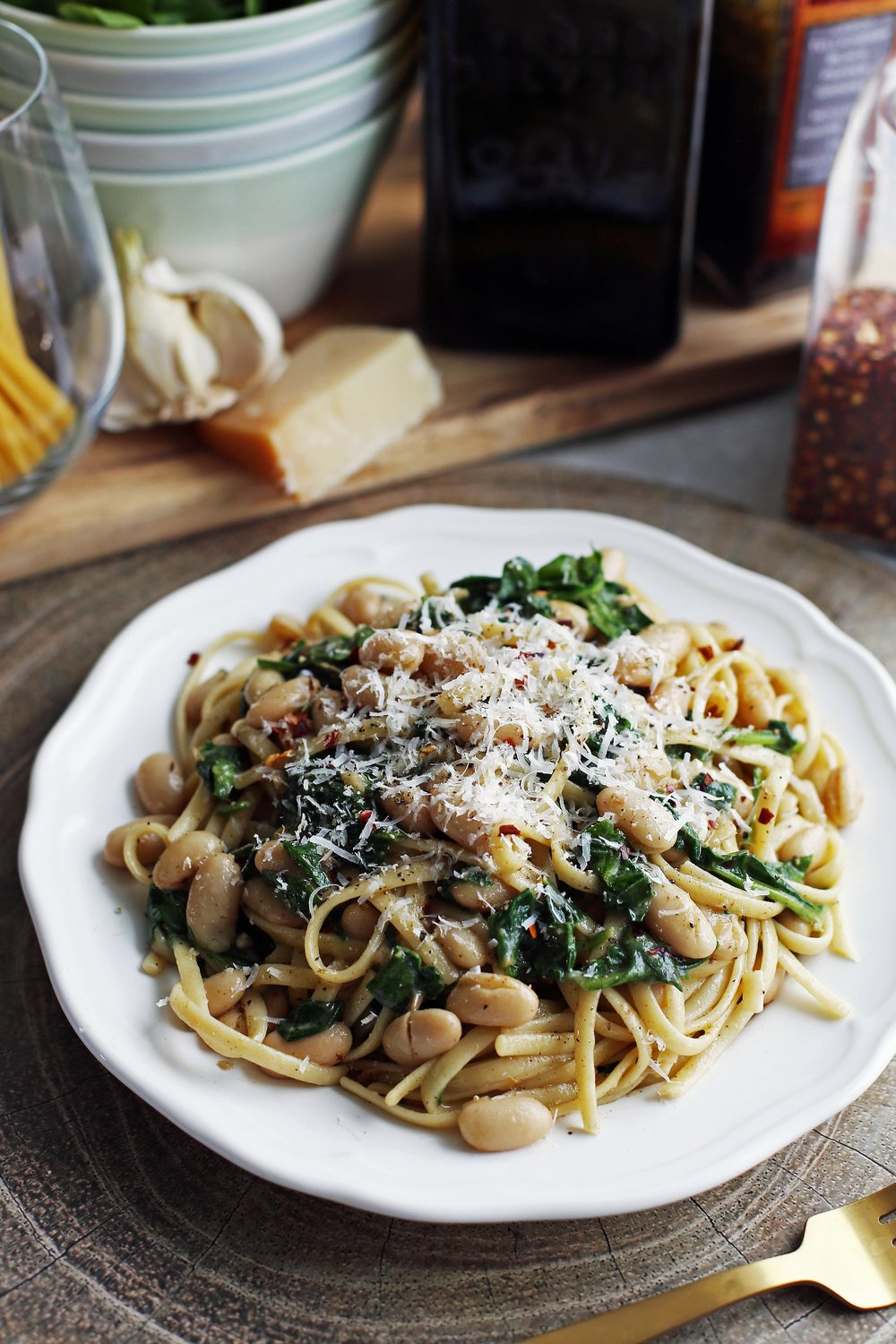 Brown Butter Linguine with White Beans and Spinach topped with parmesan cheese on a white plate.