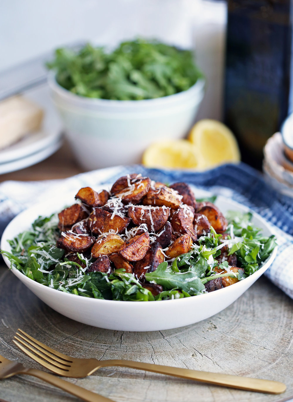 Crispy roasted spiced baby potato and arugula salad topped with parmesan cheese in a large white bowl.