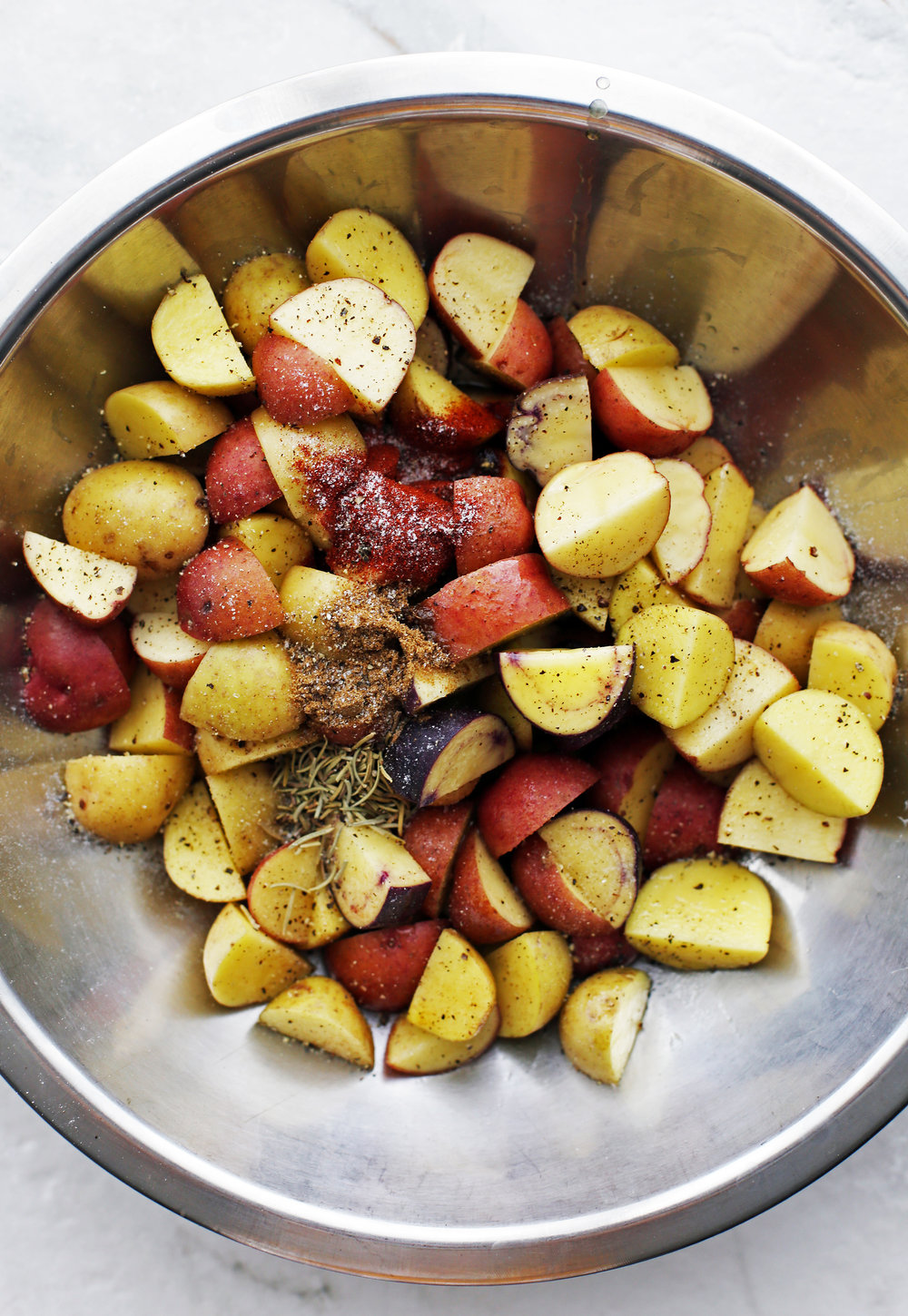 Quartered baby potatoes, olive oil, spices, and dried rosemary in a metal bowl.