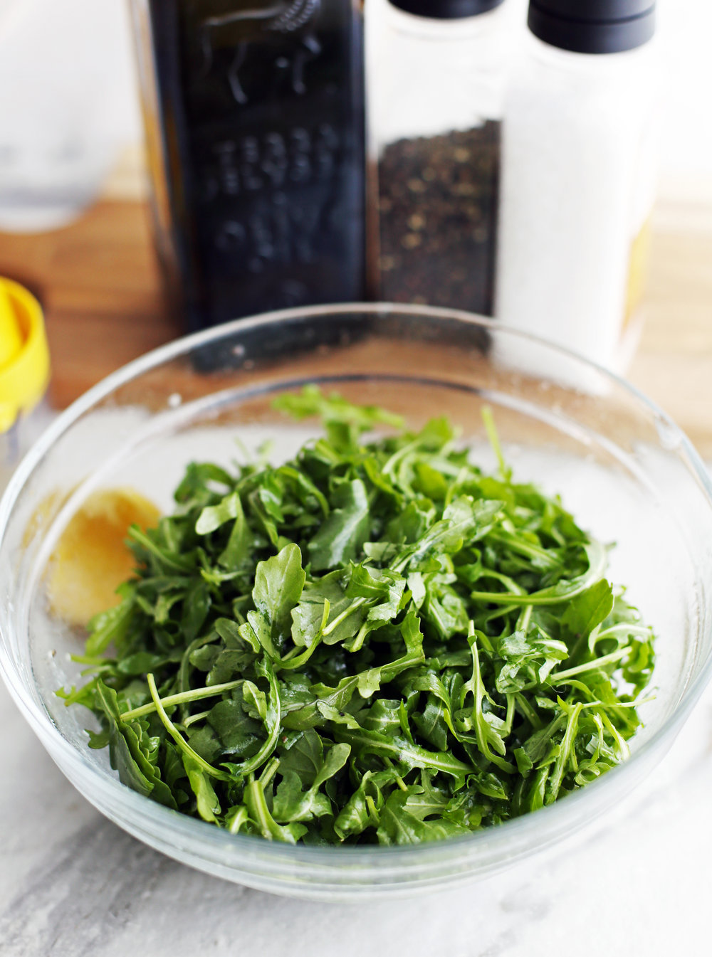 Baby arugula that has been tossed with olive oil, lemon juice, salt, and pepper in a glass bowl.