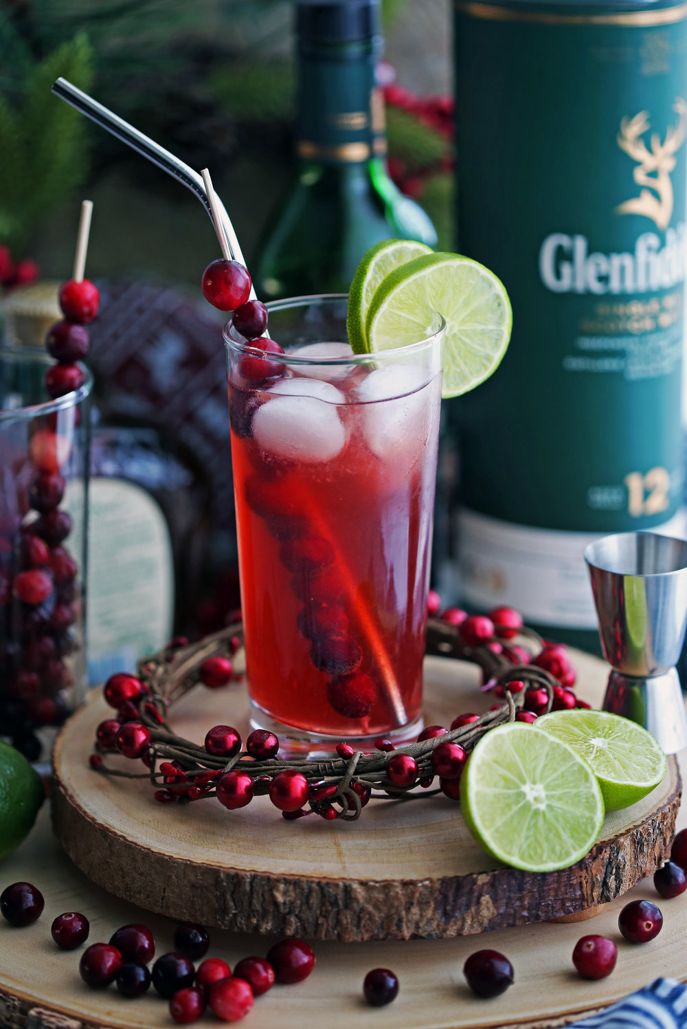 A tall highball glass full of Cranberry Whiskey Ginger Cocktail with lime slices and fresh cranberries.