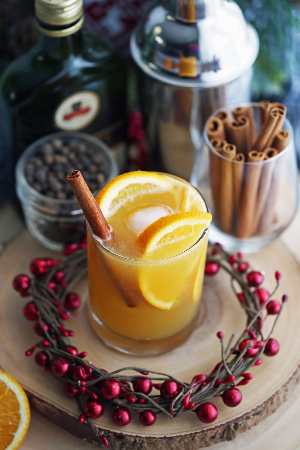 A glass of spiced orange brandy spritzer cocktail with orange slices and a cinnamon stick in it.