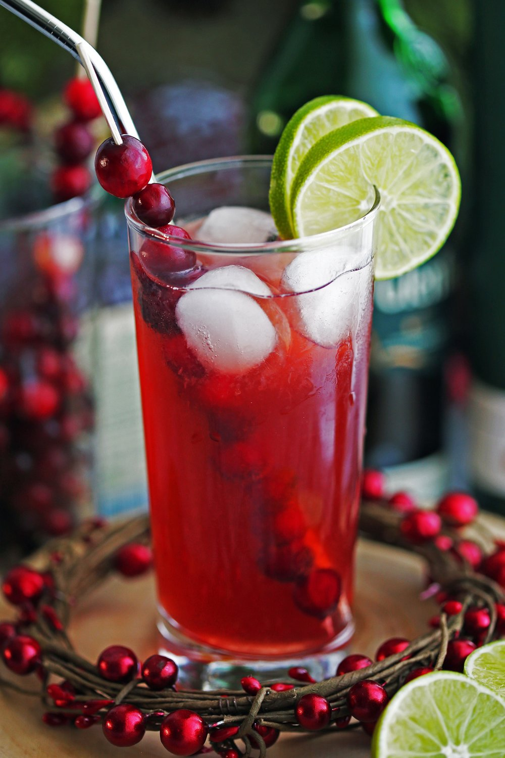 Cranberry Whiskey Ginger Cocktail in a tall highball glass with lime slices, fresh cranberries, ice cubes, and a stainless steel straw in it.