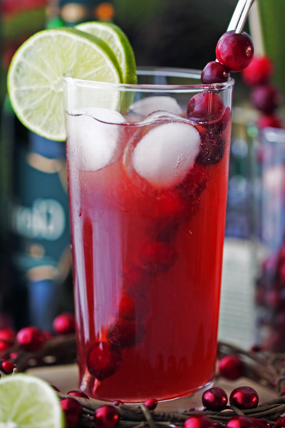 A tall highball glass of Cranberry Whiskey Ginger Cocktail with lime slices, fresh cranberries, and ice cubes.