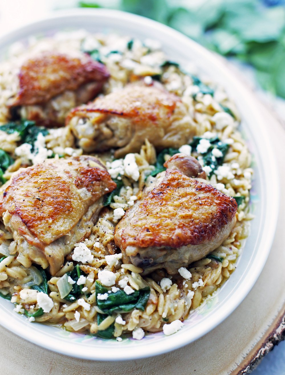 A large oval platter holding Instant Pot Lemon Pepper Orzo with Chicken Thighs.