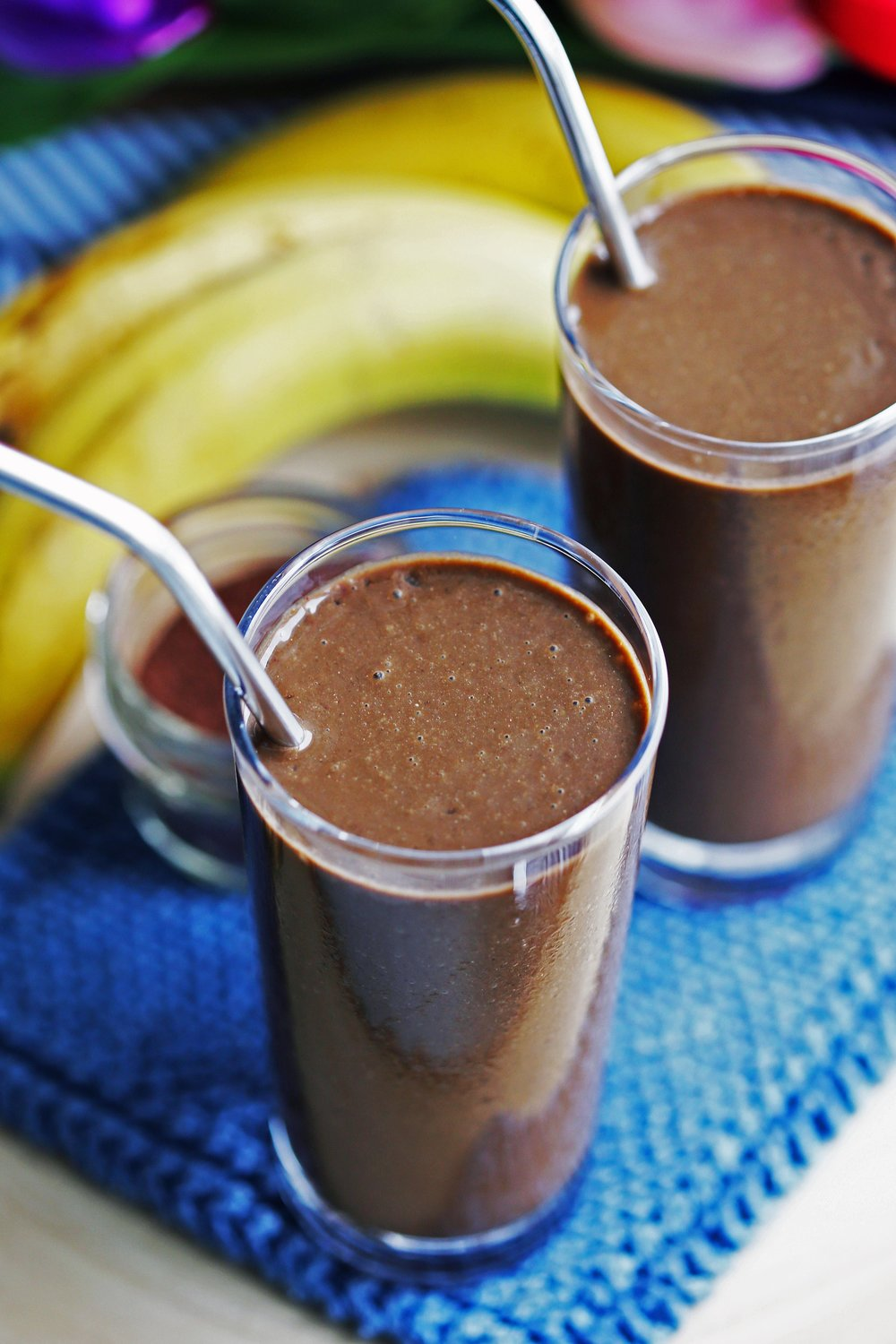 Healthy chocolate banana smoothies in two tall glasses with stainless steel straws.