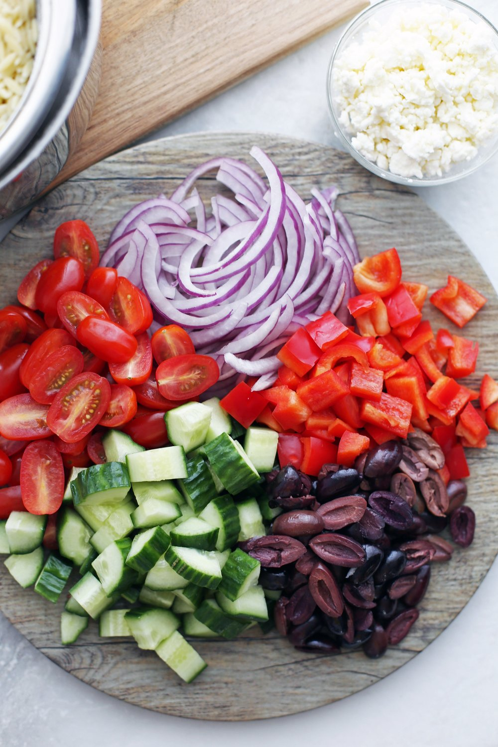 A large round wooden platter holding chopped cucumbers, grape tomatoes, red bell peppers, black olives, and red onions.