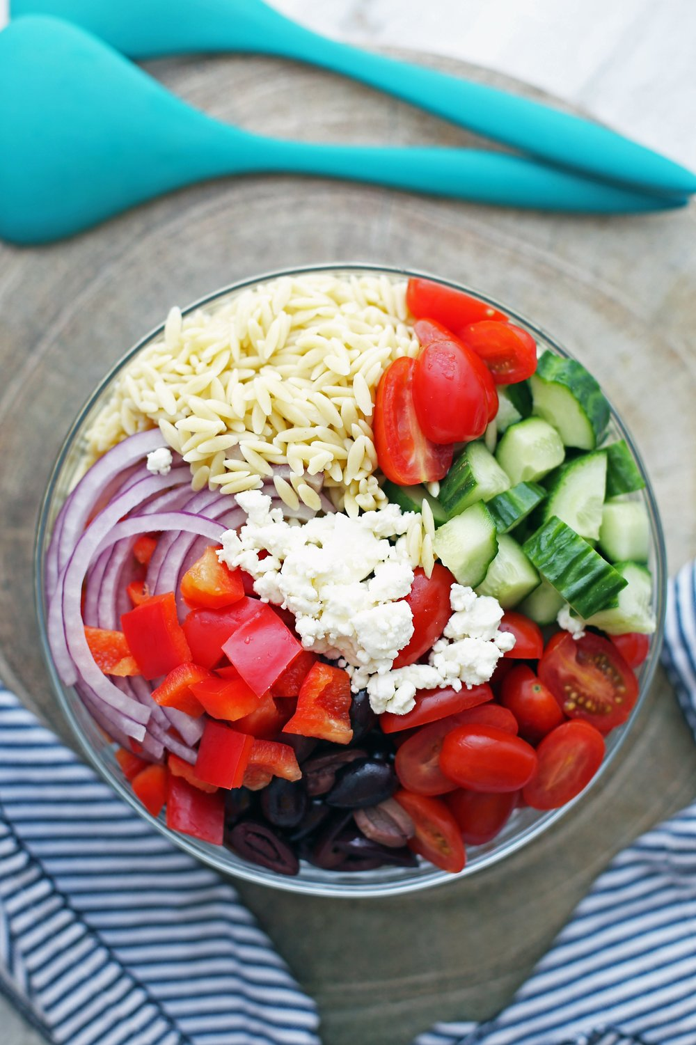 A large glass bowl containing orzo pasta, feta cheese, sliced red onions, and chopped tomatoes, olives, cucumber, and bell pepper.