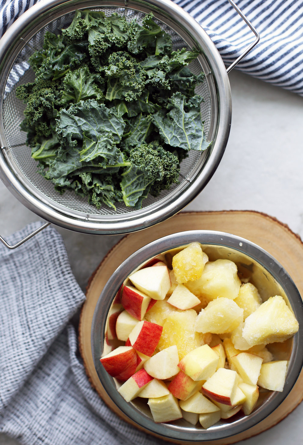 A bowl containing frozen pineapple chunks and chopped apples and a stainer containing chopped kale.