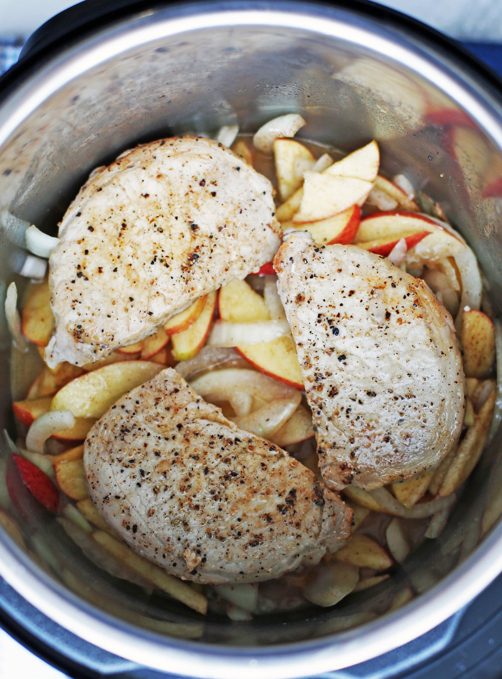 Sliced apples, sliced onions, ground cinnamon, lemon juice, salt, and chicken broth that's topped with three browned boneless pork chops in an Instant Pot.