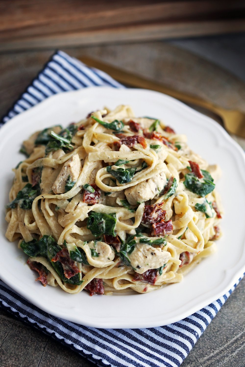Instant Pot creamy chicken fettuccine with spinach and sun-dried tomatoes on a white plate.