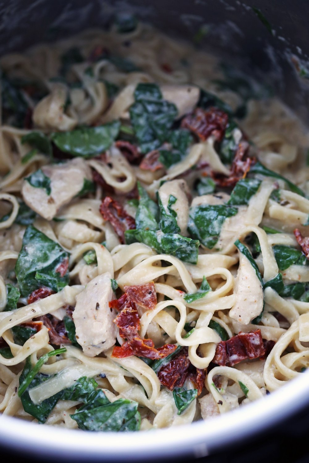 Creamy fettuccine pasta tossed in a creamy sauce with chicken, sun-dried tomatoes, and baby spinach in the Instant Pot.