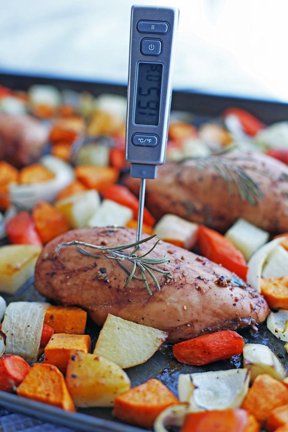 """A digital instant read thermometer inserted into a baked balsamic chicken breast that reads """"165 degrees Fahrenheit."""""""