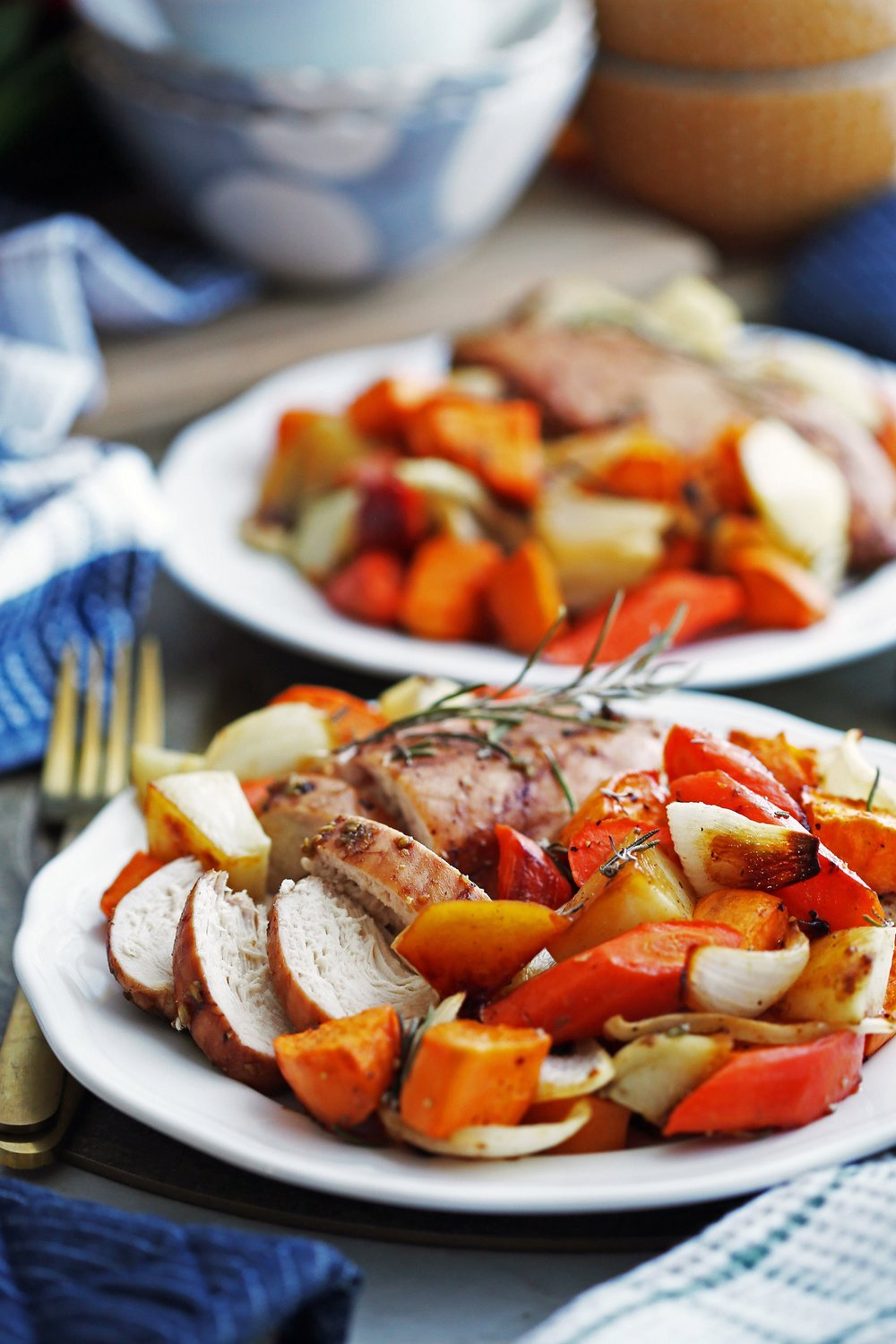 Sheet pan balsamic chicken, roasted carrots, potatoes, sweet potatoes, and onions on two white plates.