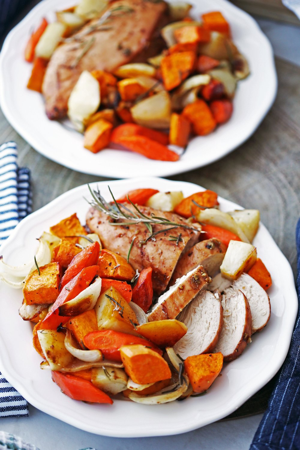 Two white plates containing baked balsamic chicken breasts and roasted vegetables, including potatoes and carrots.