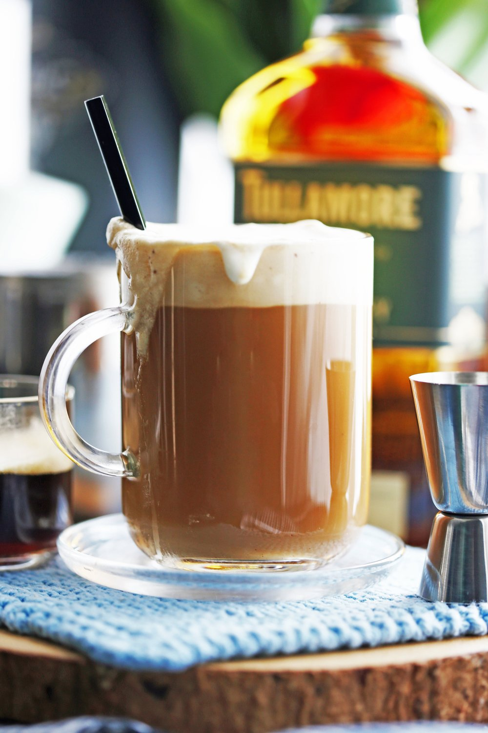 A stirred cup of Maple Irish Coffee in a glass mug with a spoon in it.