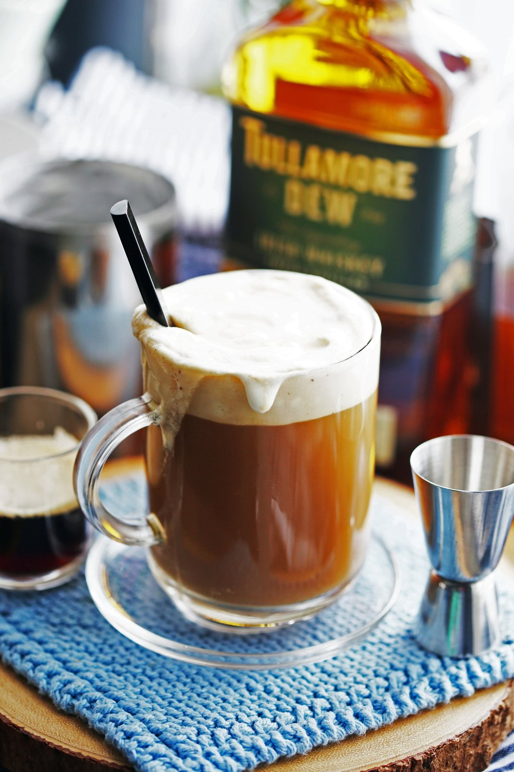 A glass mug filled with Maple Irish Coffee, gently stirred, with a black stirring spoon in it.