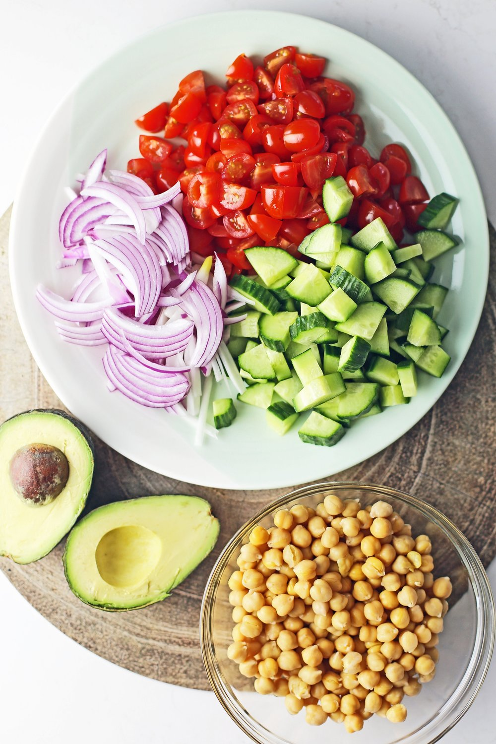 A large plate containing chopped and sliced English cucumber, grape tomatoes, and red onions, a bowl of cooked chickpeas, and an avocado cut in half.