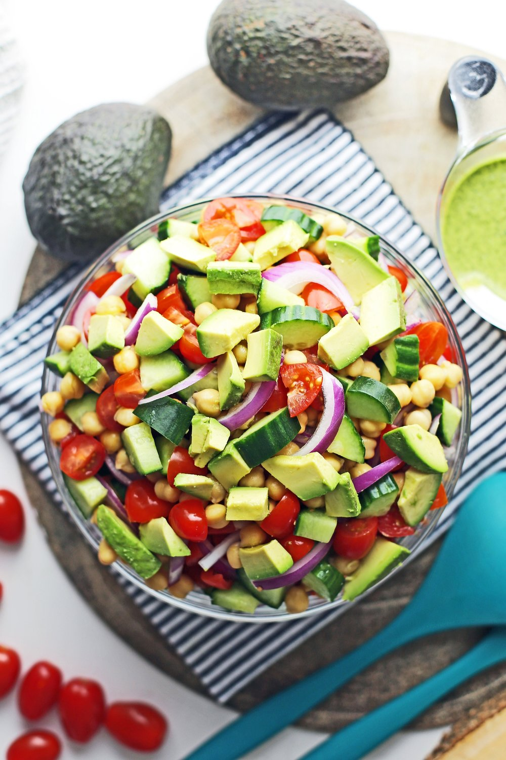 Overhead view of cooked chickpeas and chopped and sliced cucumber, avocado, tomatoes, and red onions.