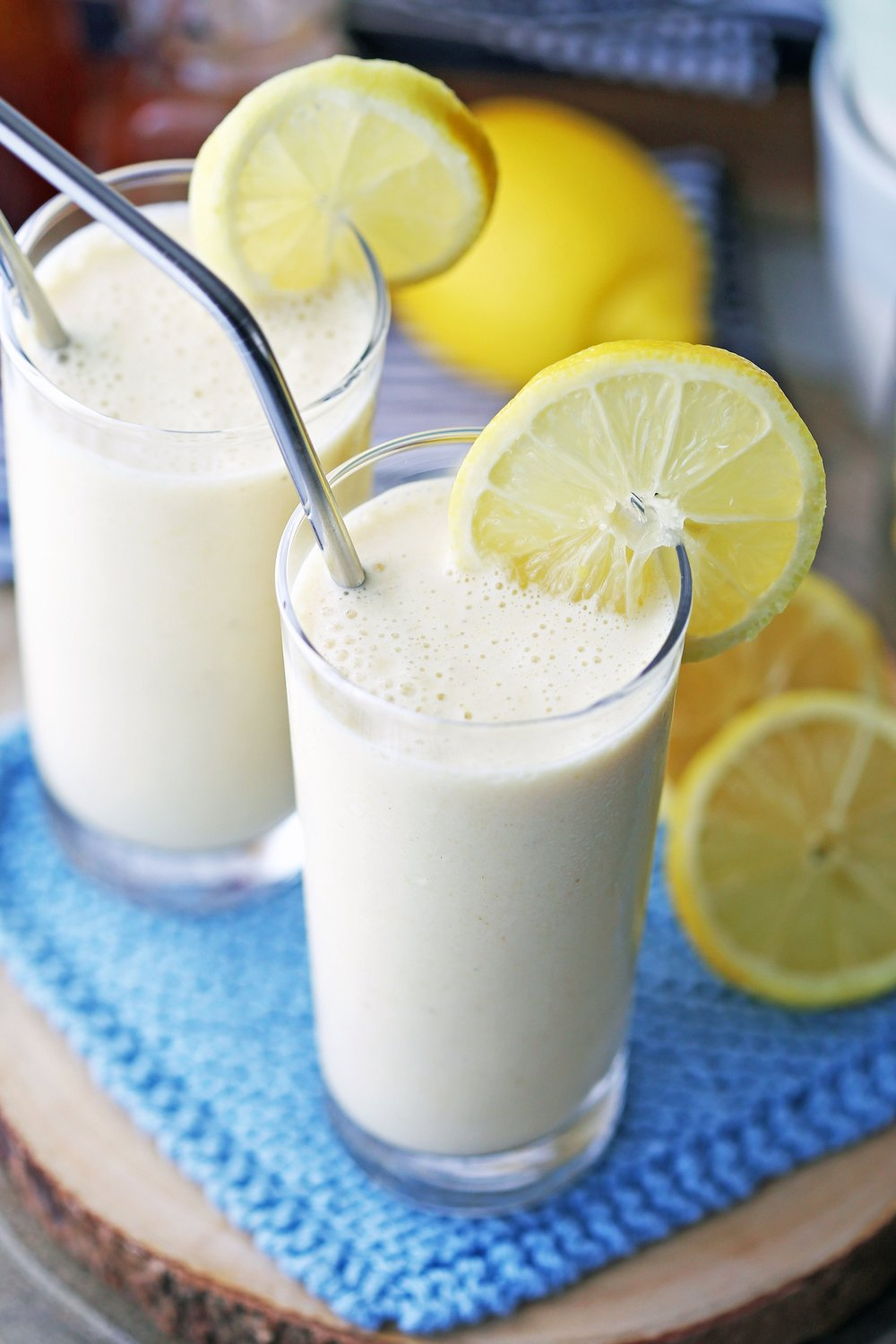 Two tall glasses filled with Lemon Pineapple Smoothies that's garnished with lemon slices.