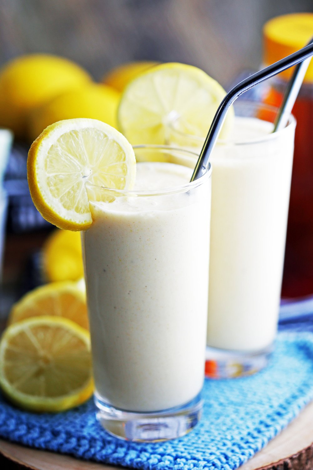 Lemon Pineapple Smoothie drinks in tall glasses with metal straws and lemon slices on the rim.