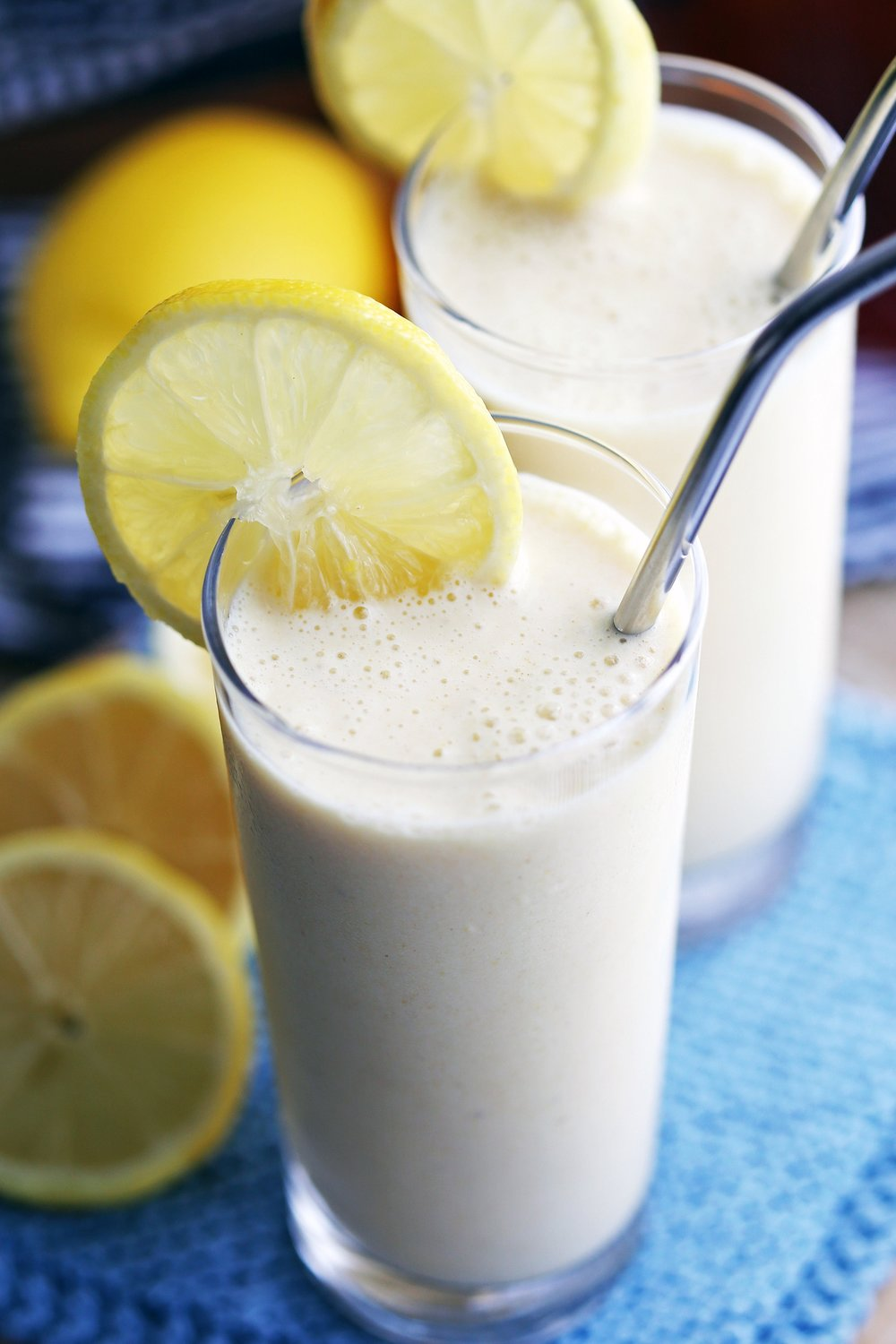 A closeup of lemon pineapple smoothie in a tall glass with metal straw and lemon garnish with another similar glass behind it.