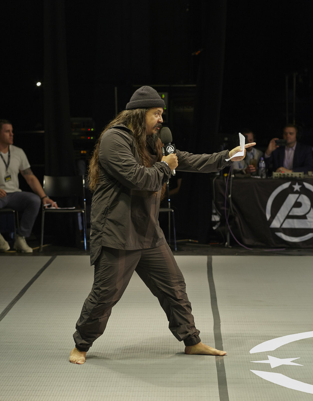 "Announcer Tone Anderson lets the Polaris crowd in on ""Elite clothing for combat sports aficionados…"""