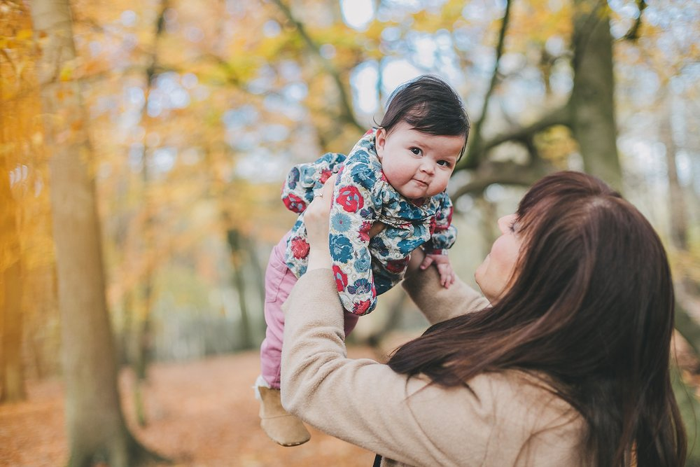 Mum and baby in Campton woods in Autumn.  Mum lifting baby into the air, surrounded by autumn leaves. Bedfordshire Family Photography.