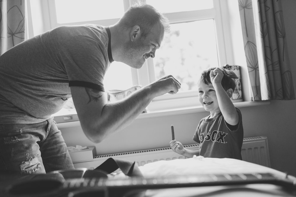 Dad fist bumping young son at home in Bedfordshire.  Family photography at home by Jane Morgan Photography.