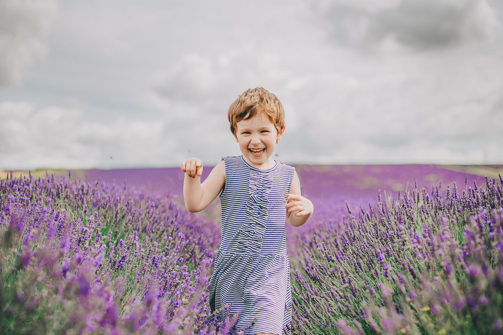 Little girl in a striped dress running through Hitchin Lavender Fields on a sunny day.  Family photography in Hitchin by Jane Morgan Photography.