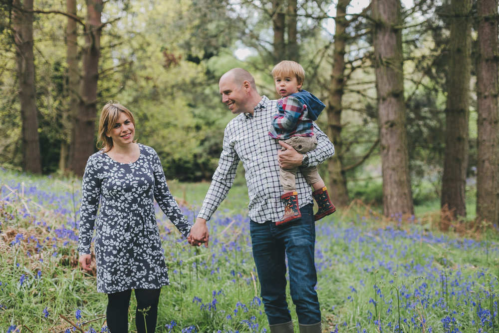 A mother, father and son standing in the bluebells in Maulden Woods near Ampthill.  Family Photo Session by Jane Morgan.