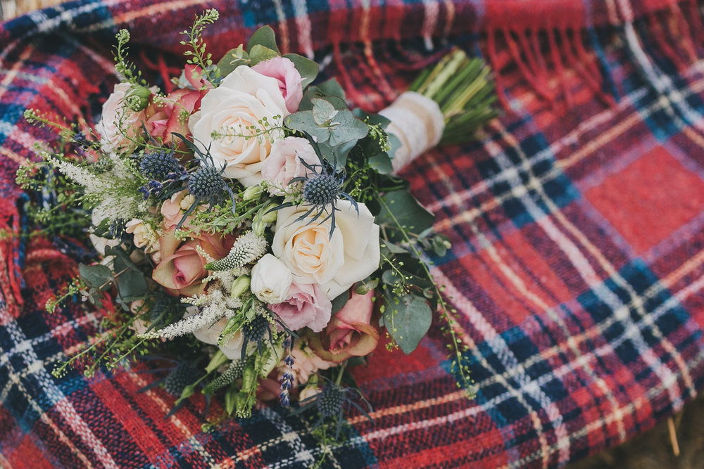 Rose, eucalyptus and thistle bouquet lying on red tartan blanket