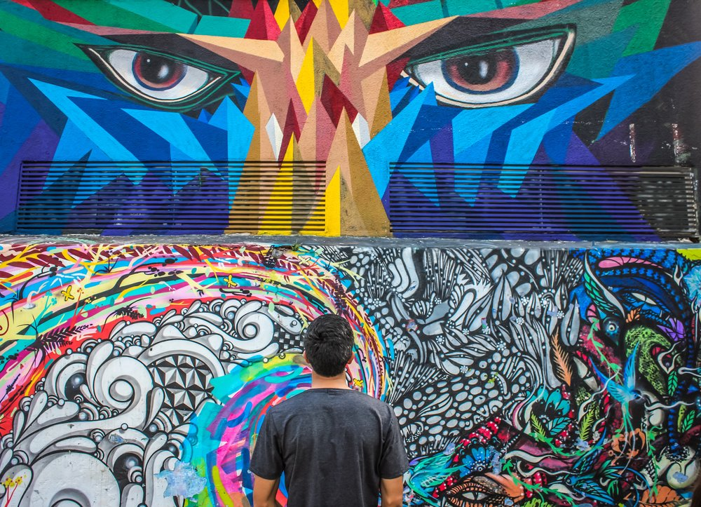 A man stares at a large, colorful mural of a pair of eyes and psychedelic shapes.