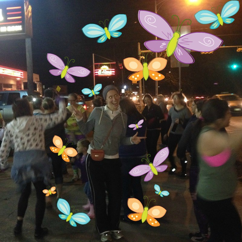 A woman dances with a group of other dance walkers on a sidewalk at night. Cartoon butterflies surround her.