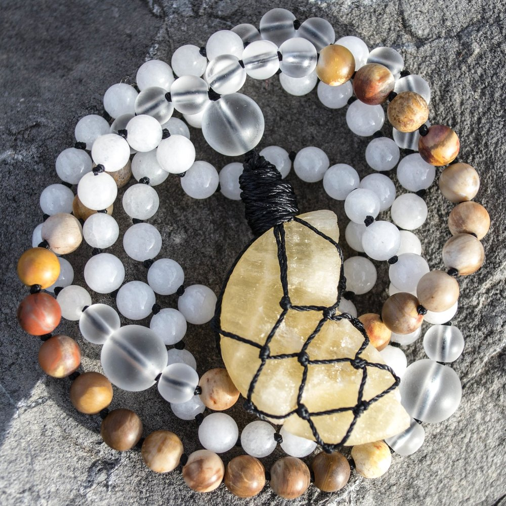Mini Mala creations crafted with a crescent moon calcite pendant. Consists of Petrified wood, white jade, and frosted quartz beads.