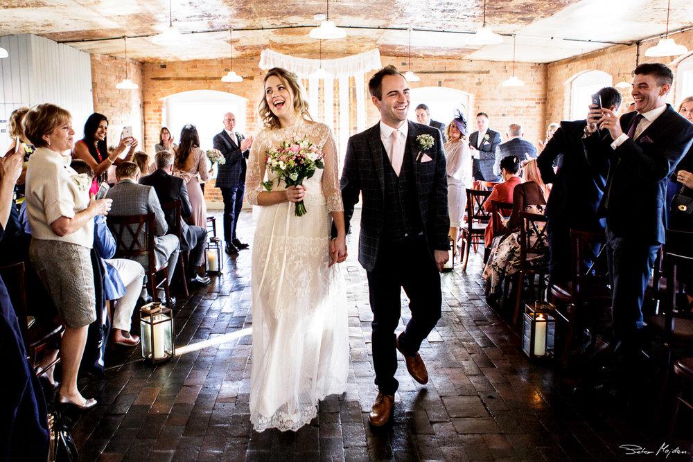 happy couple leaving wedding ceremony