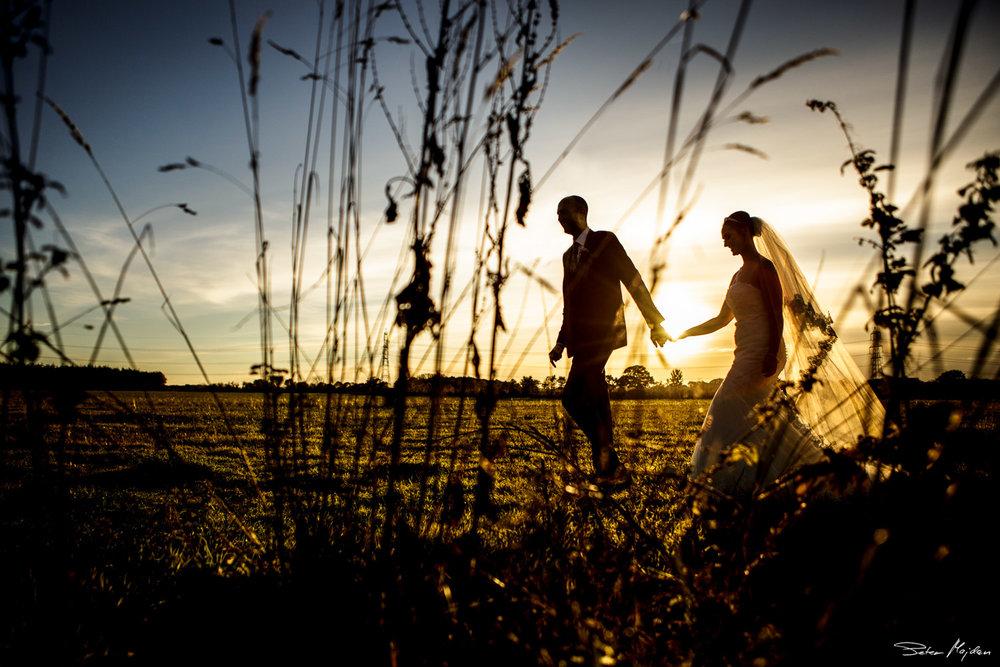 wedding couple walking across fields