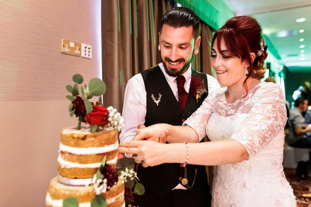 newlywed cutting cake at eastwood hall