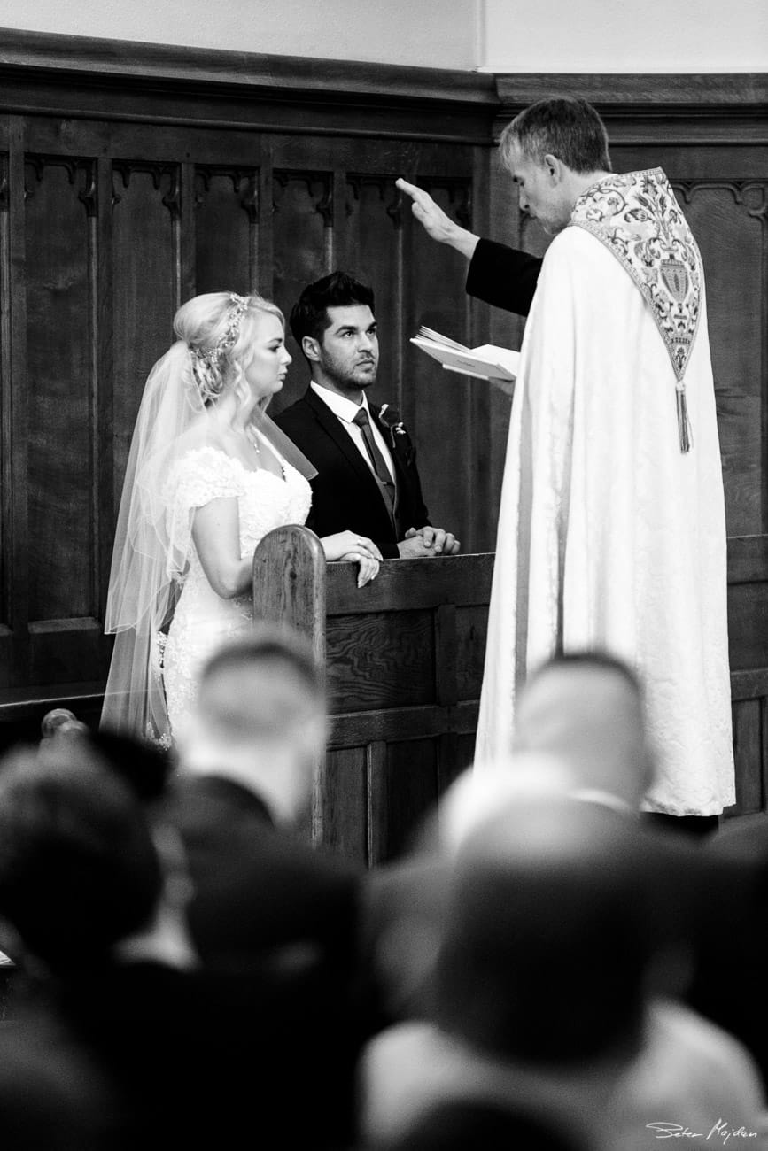 vicar giving blessing to bride and groom